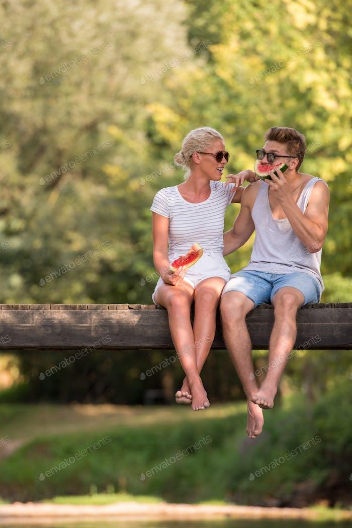 pareja disfrutando de sandía mientras se sienta en el Puente de De madera