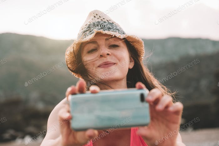 Beautiful smiling girl taking a picture with her smartphone. Pretty woman has fun.