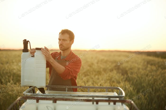 Young Farmer Filling Watering Can in Field