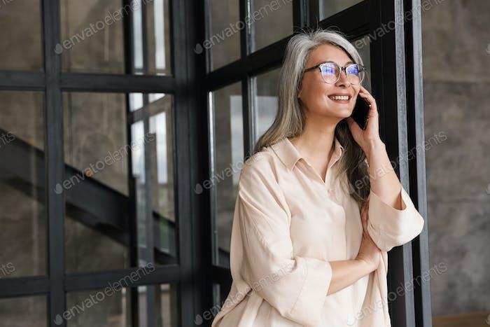 Happy pretty woman talking by mobile phone