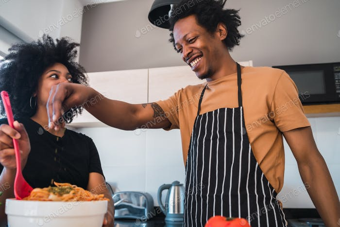 Afro couple cooking together in the kitchen.