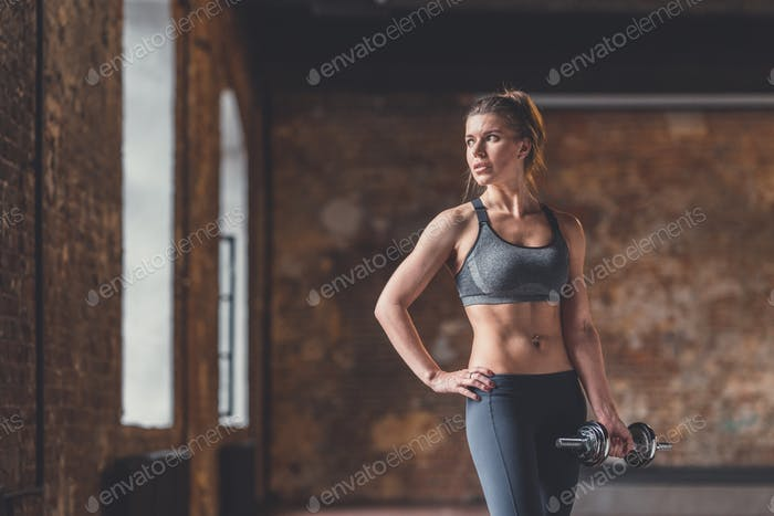 Young athletic girl with dumbbells in the loft