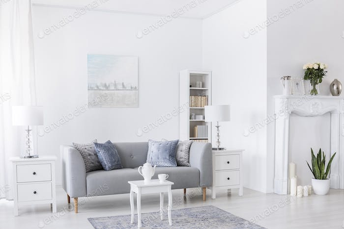 Table on carpet in front of grey settee in white living room int