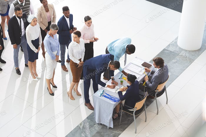 High angle view of diverse business people checking in at conference registration table in  lobby
