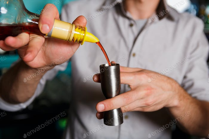 Young Barman's making shot cocktail, pouring syrup into glass