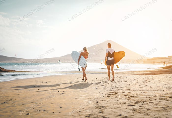 Happy surfers running with surfboards on the beach