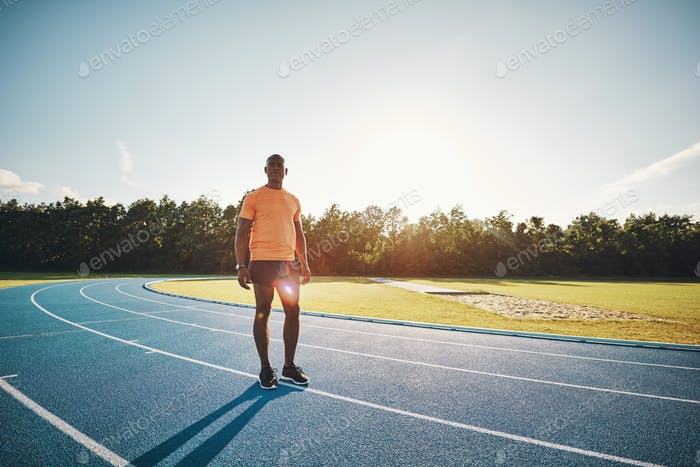 Focused young runner standing alone on a track