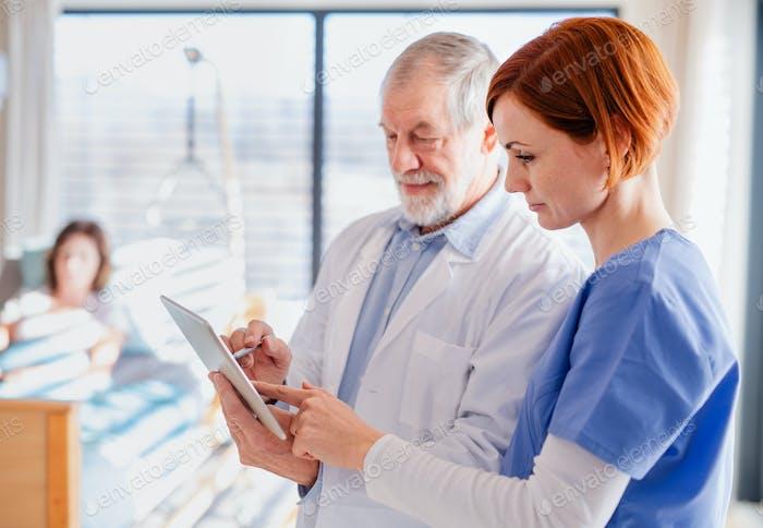 Porträt eines älteren männlichen Arztes stehend im Krankenhauszimmer, im Gespräch mit einer Krankenschwester.