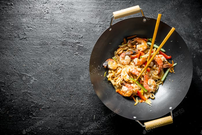 Chinese Udon noodles in a wok pan with chopsticks.