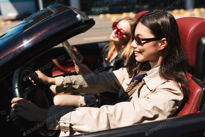 Smiling girl in sunglasses happily driving cabriolet car with fe
