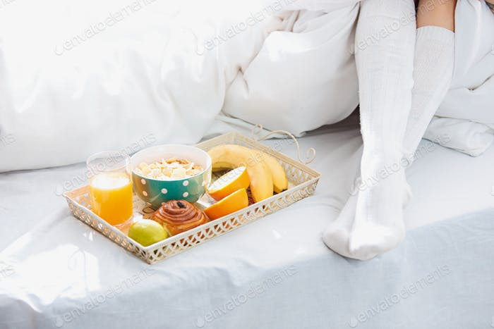 Partial view of female legs and breakfast on bed