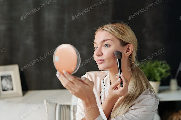 Pretty woman with brush applying powder on her face and looking in mirror