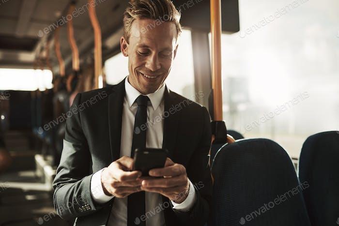Lächelnd junge Geschäftsmann Lesen von Textnachrichten während seiner morgendlichen pendeln
