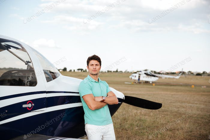 Serious man standing with arms crossed near small plane