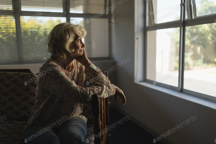 Side view of thoughtful senior woman relaxing in living room at nursing home
