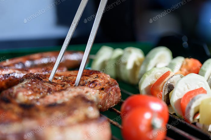 close up of roasted meat pricked by carving fork on barbecue grill