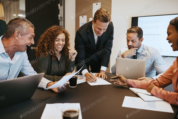 Smiling businesspeople sitting in an office boardroom discussing paperwork