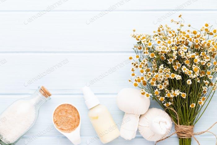 Sea salt, chamomile aromatherapy oil in bottles on vintage wooden background.