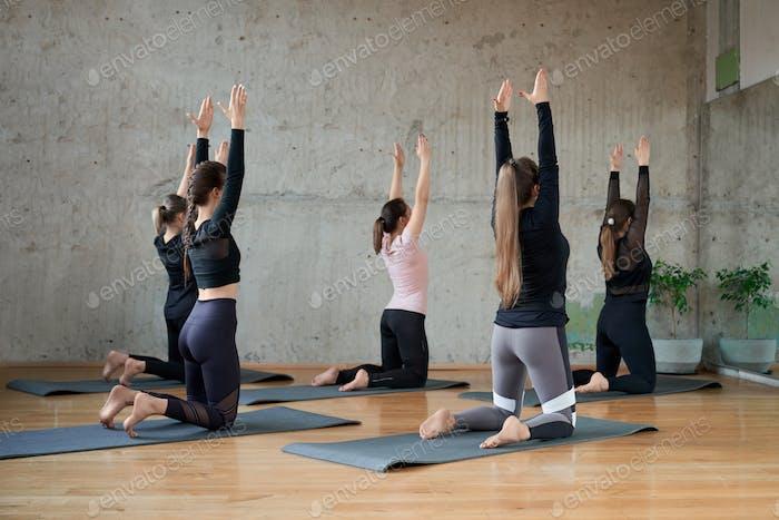 Junge Frauen praktizieren Yoga in der Halle
