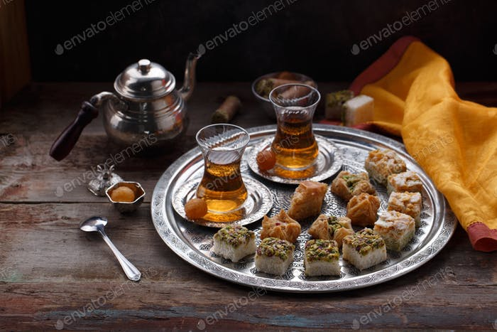 Oriental sweets and tea, copy space, dark photo