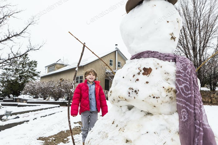 A six year old boy building a snowman