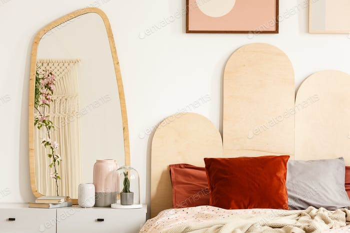 Red cushions on bed with headboard next to dressing table with m