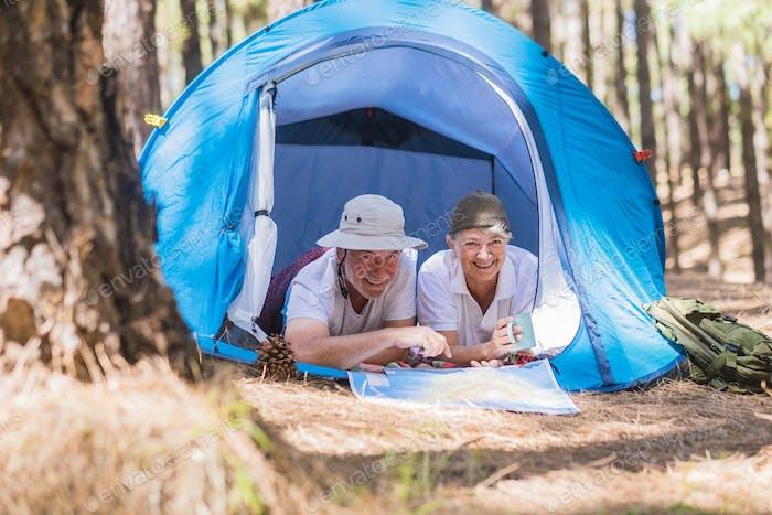 Couple of active traveler senior people enjoy together inside a tent