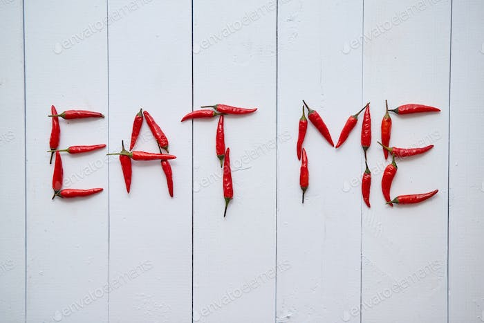 A word EAT ME formed with small red chilli peppers. Placed on white wooden table
