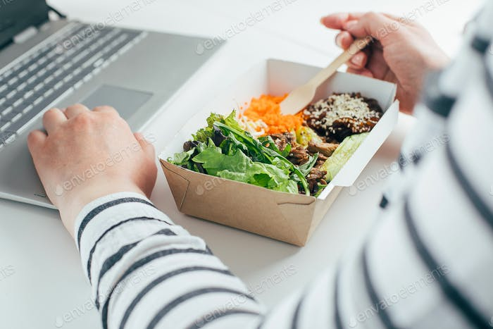 Woman having lunch in recycled bowl using laptop. Food delivery, quarantine, take out food concept