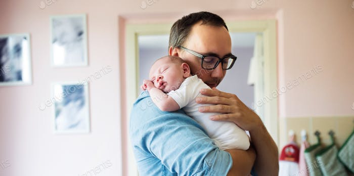Young father holding newborn baby son in his arms