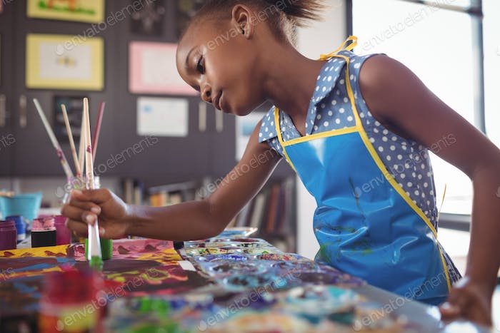Focused elementary girl painting at desk