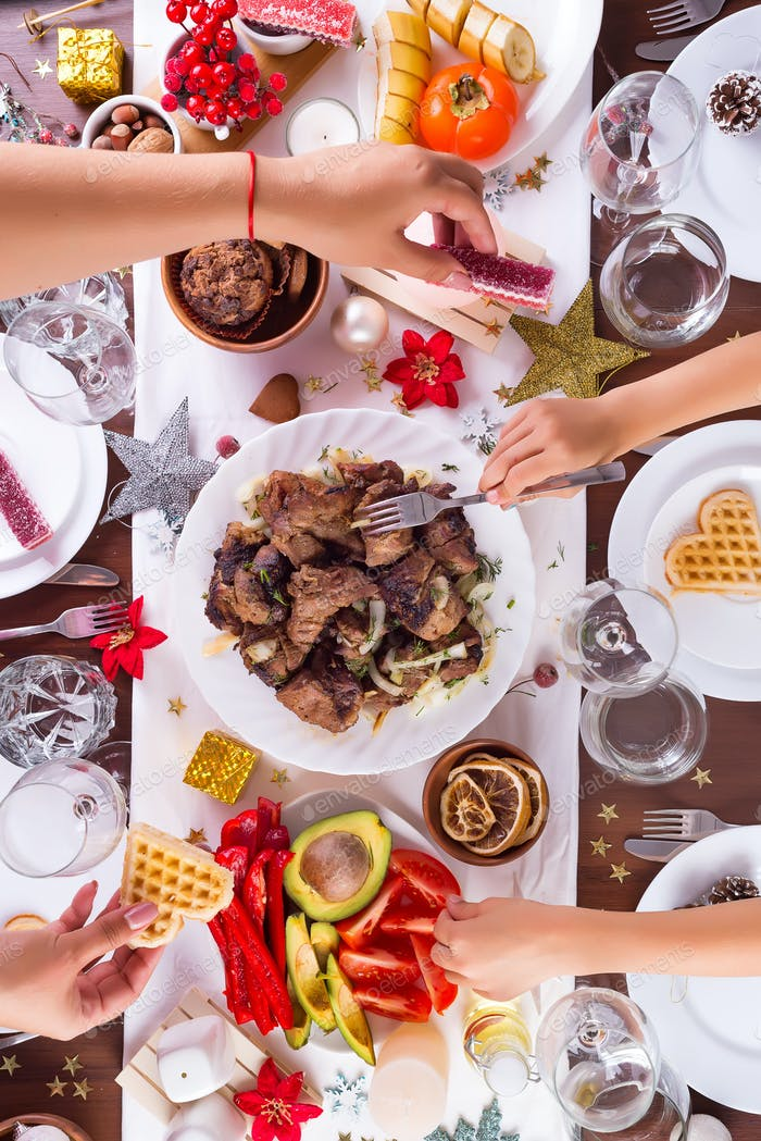 Christmas table setting with food on a plate, mom and child hands handing food and decoration on
