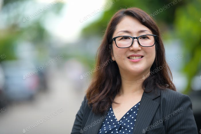 Mature happy beautiful Asian businesswoman smiling and thinking in the streets outdoors