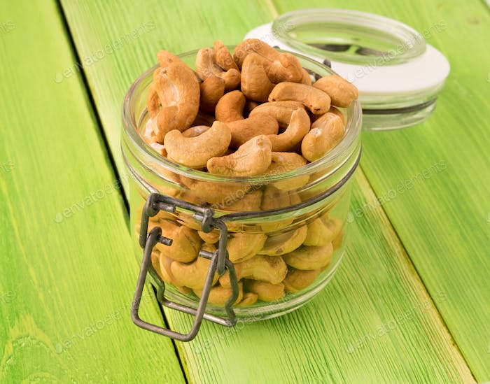 glass jar with cashew nuts and green wooden background, side view