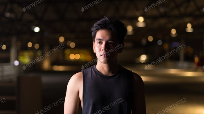 Portrait of young handsome Asian man thinking outdoors at night