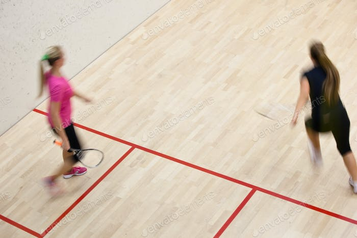 Two female squash players in fast action on a squash court (moti