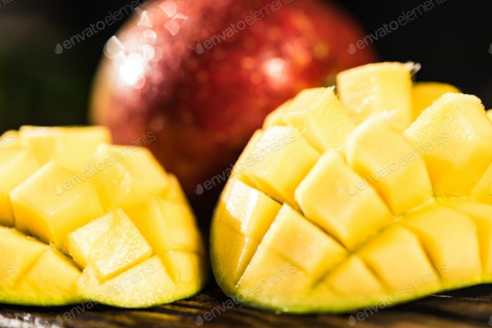 Whole and cut mango on a dark wood background
