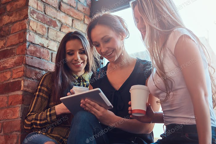 Group of female friends discussing while looking something on a digital tablet in a apartment