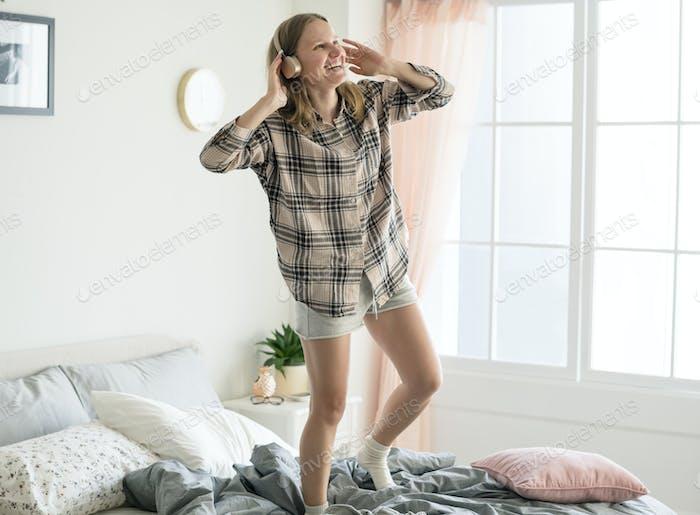 Caucasian girl dancing on bed