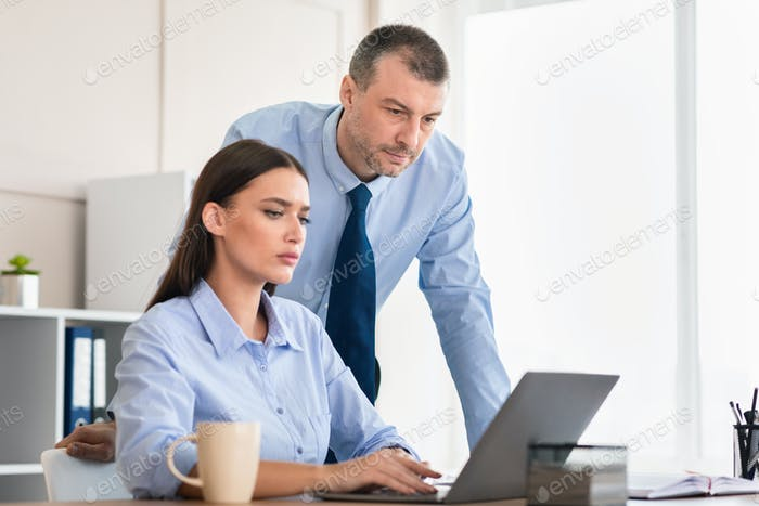 Manager Checking Female Employee During Work At Laptop In Office