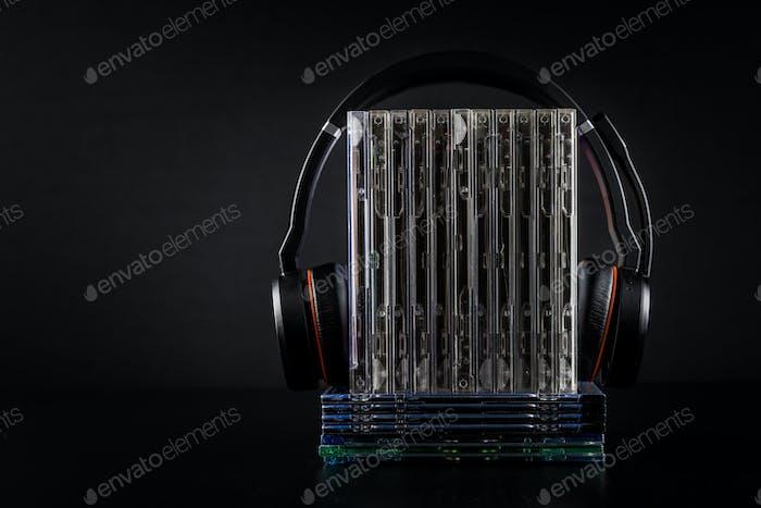 Hi-Fi-Kopfhörer auf CDs auf schwarzem Hintergrund mit Kopierplatz.