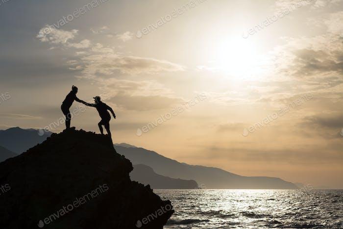 Teamwork couple climbing hiking with helping hand