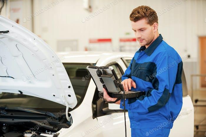 Mechanic examining car.