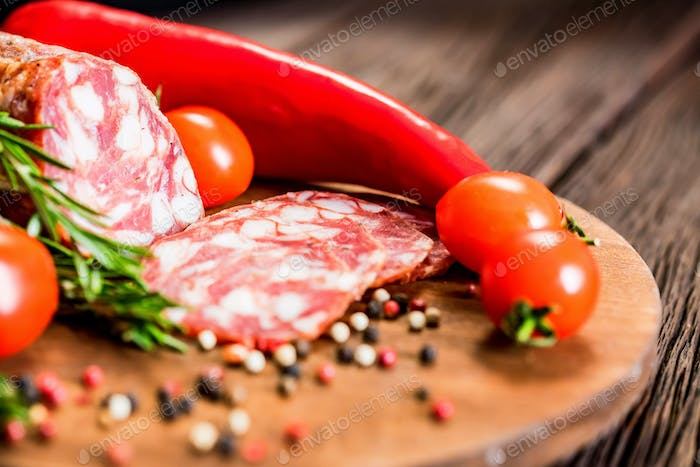 Tasty salami with tomatoes and peppercorn close