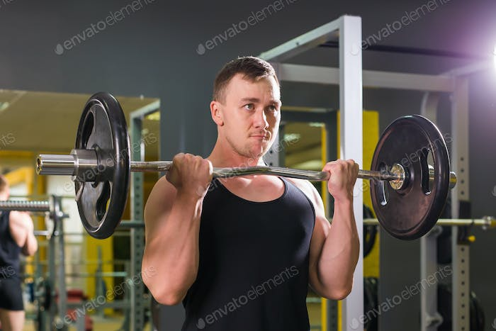 Strong man - bodybuilder with dumbbells in a gym, exercising with a barbell.