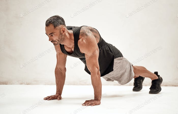 Strong and muscular athlete posing in a bright studio while doing a plank excersise