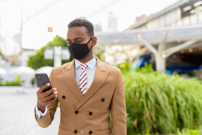 Young African businessman using phone with mask for protection from corona virus outbreak in the