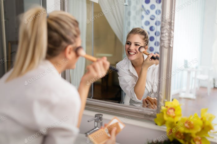 Beautiful girl in bathroom applying makeup