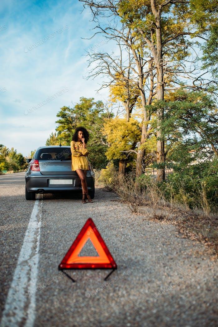 Frau mit gebrochenem Auto und Dreieck