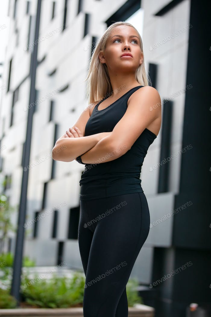 Fit Woman with Arms Crossed Standing Against Futuristic Modern Building In City